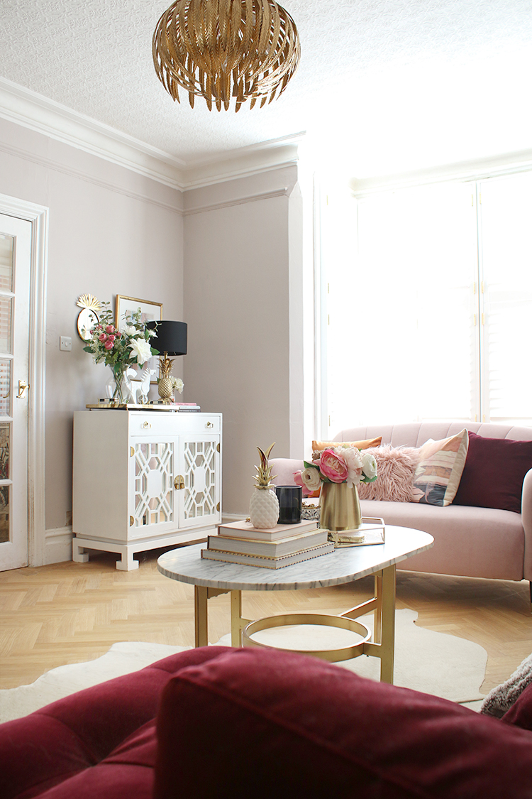 living room organising tips - vintage cabinet in room with pink sofa and gold light fixture