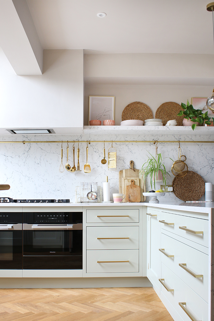 pale green kitchen with parquet flooring and open shelving