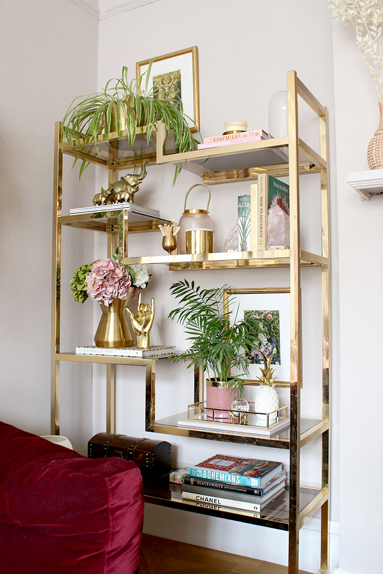 vintage brass shelving unit styled with books art and candles