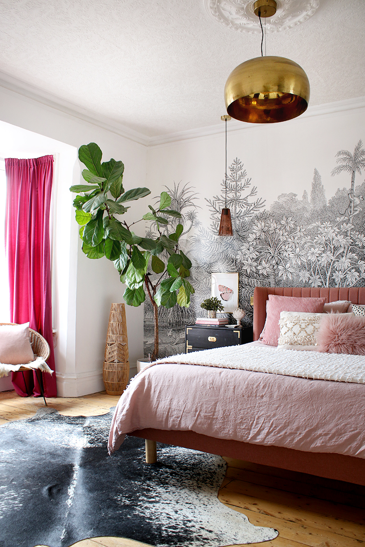 bedroom with pink bed and black and white mural with gold light fixture