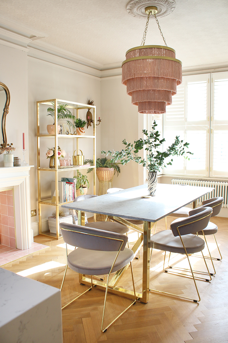 dining room with large pink light fixture, marble and gold dining table with grey velvet chairs