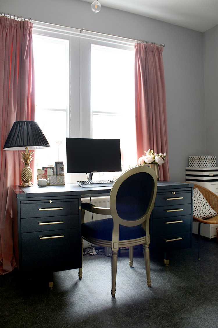 office with black desk and pink curtains