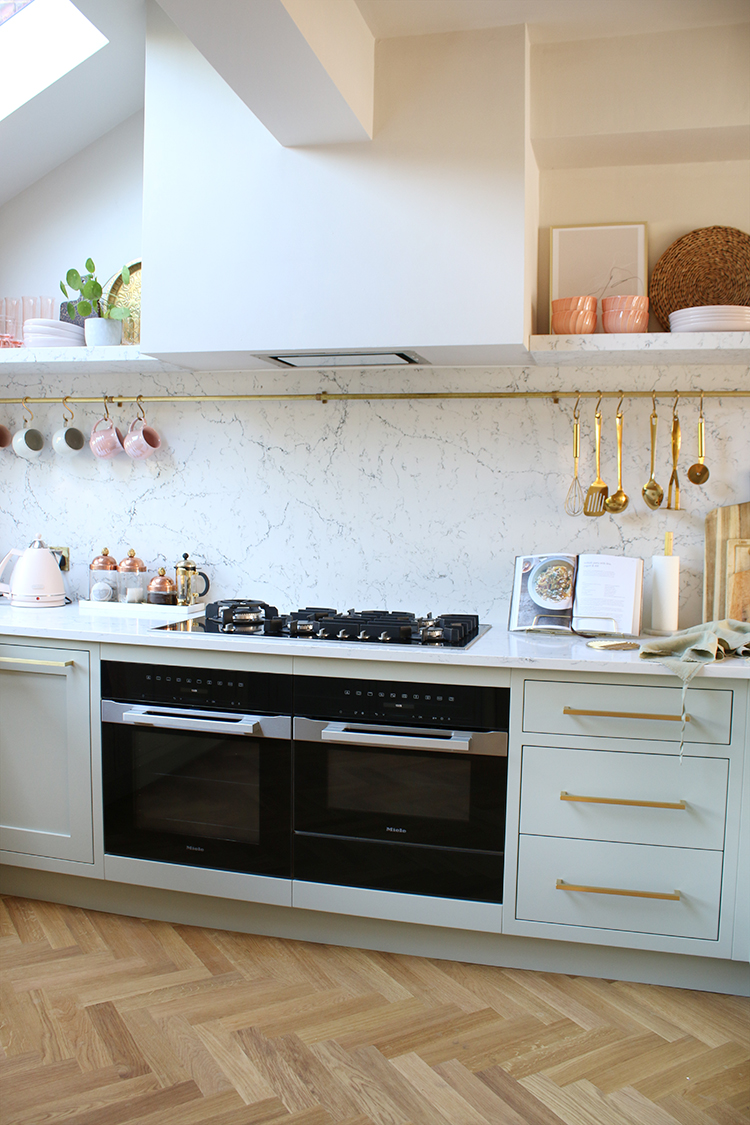 pale green and marble kitchen with pink and gold accents