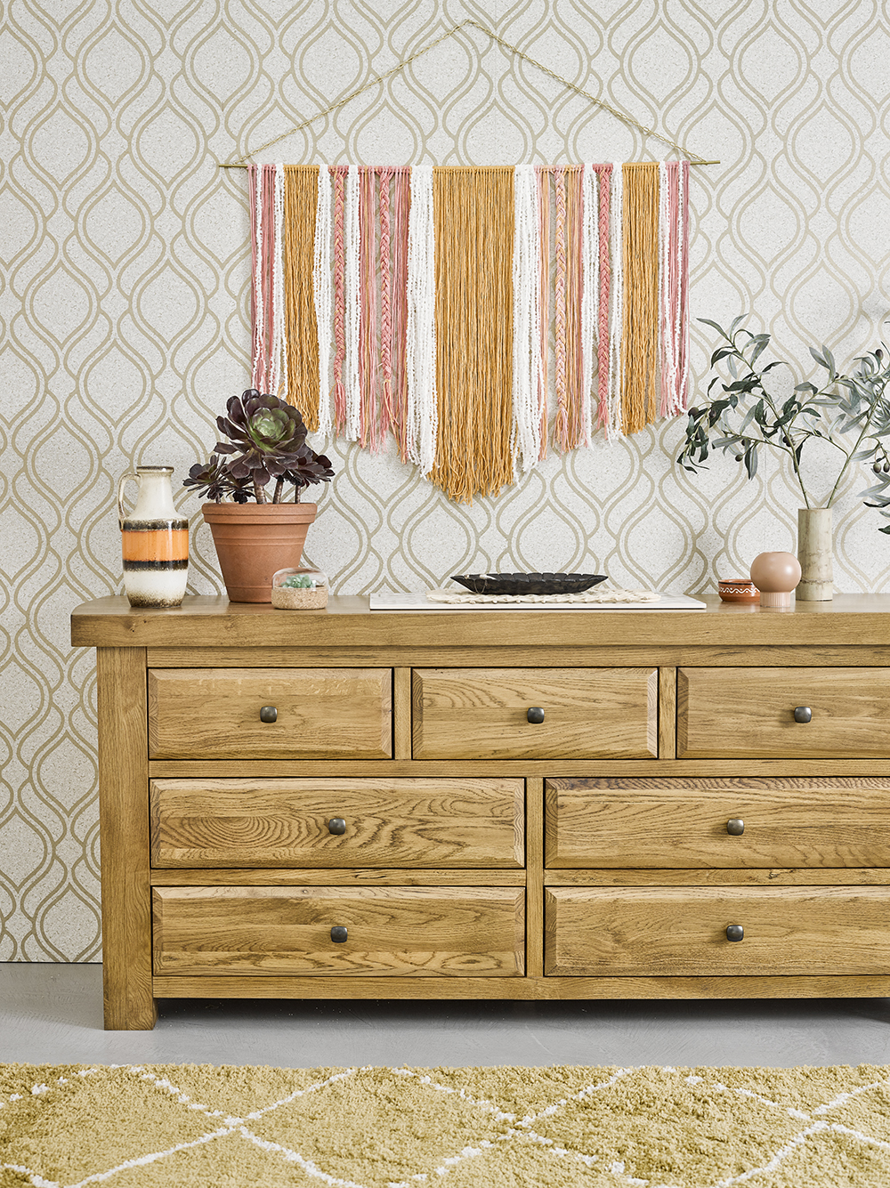 Oak chest of drawers with peach and yellow accessories