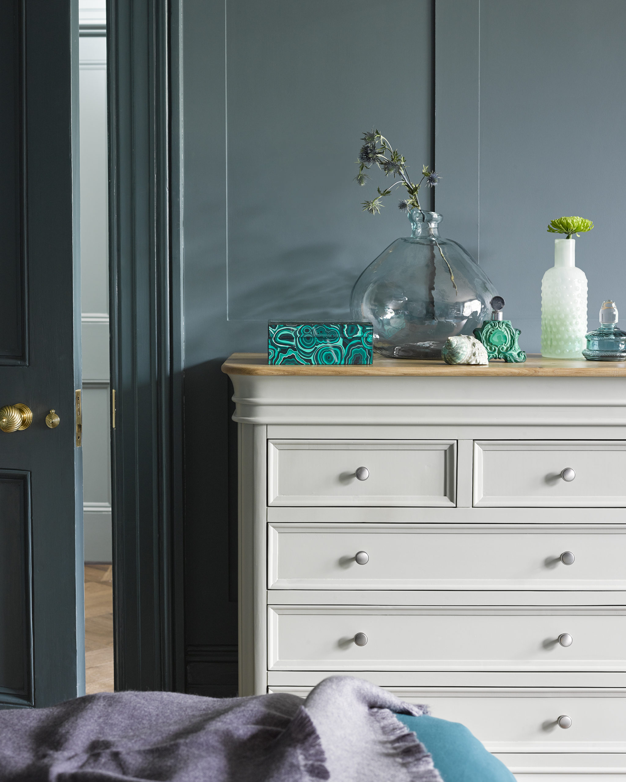 White chest of drawers against deep green-blue walls in bedroom