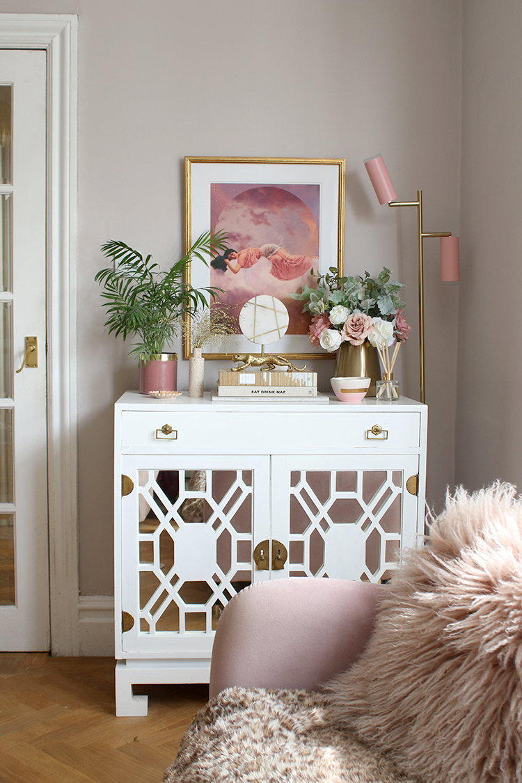 vintage white cabinet with styled accessories in pink and gold