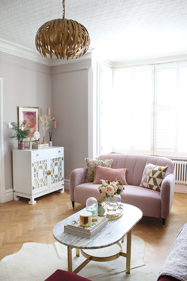 Pink sofa in living room with parquet floor and high ceilings
