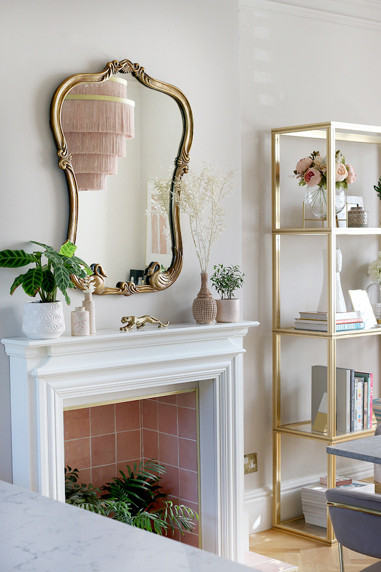 dining room with pink fireplace and gold shelving unit