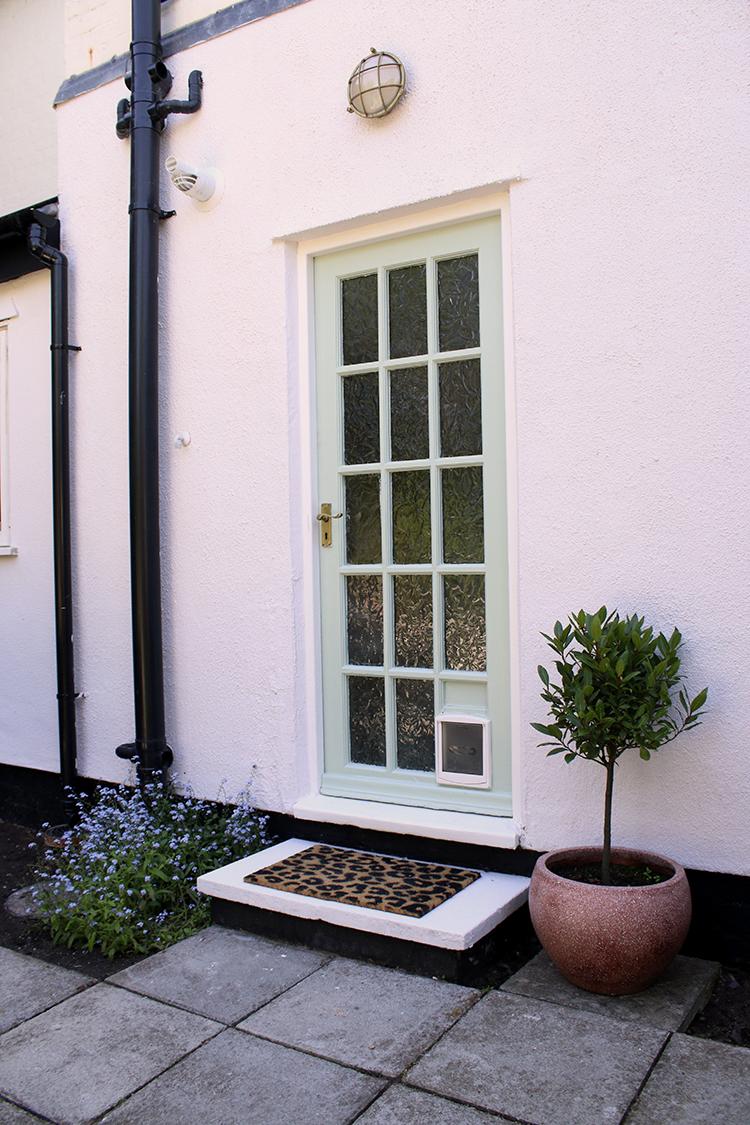 Glazed back door in pale green with leopard print door mat and bay tree in pink pot