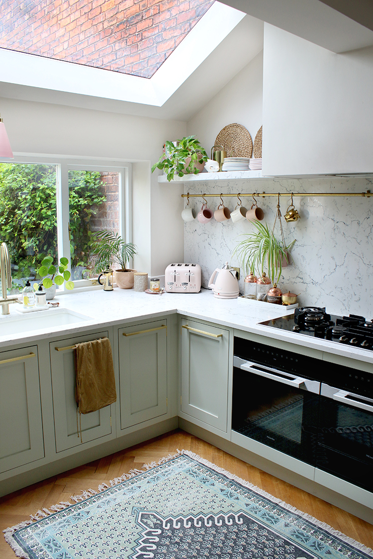Pale green kitchen with marble worktops and styled shelves