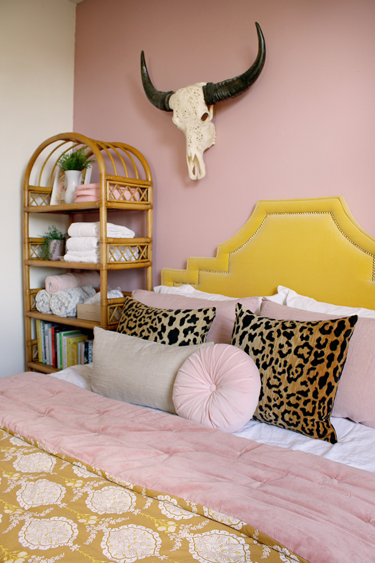 pink walls and yellow velvet bedroom with rattan bookshelf