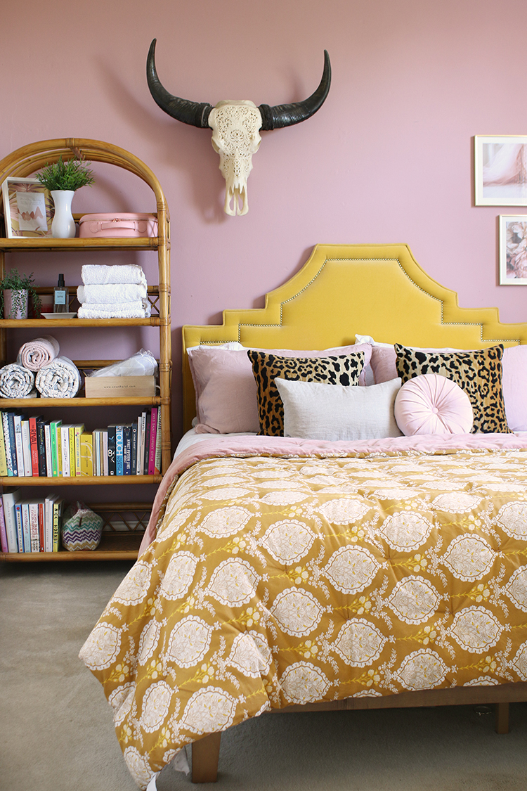pink bedroom with golden yellow velvet headboard, pink and mustard pattern bedspread and vintage rattan shelving unit