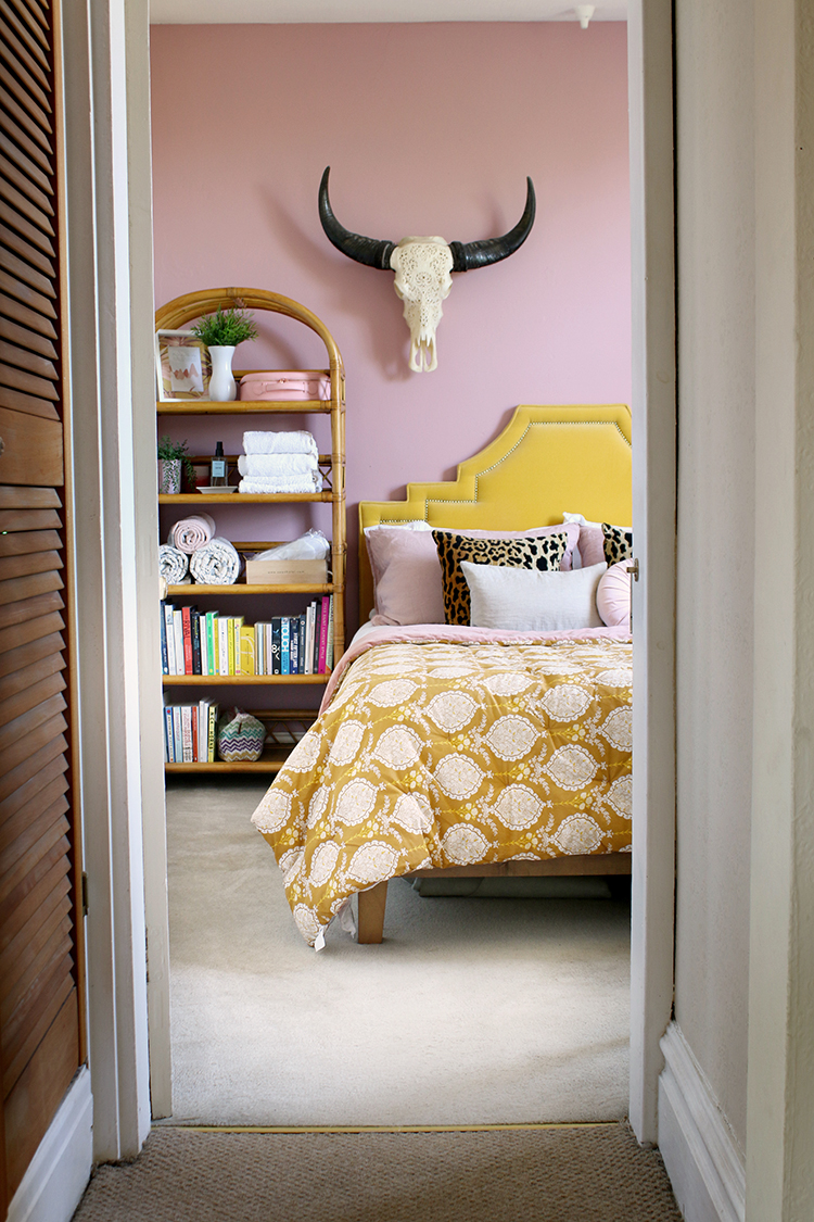 view from hallway into pink bedroom with mustard and rattan accents