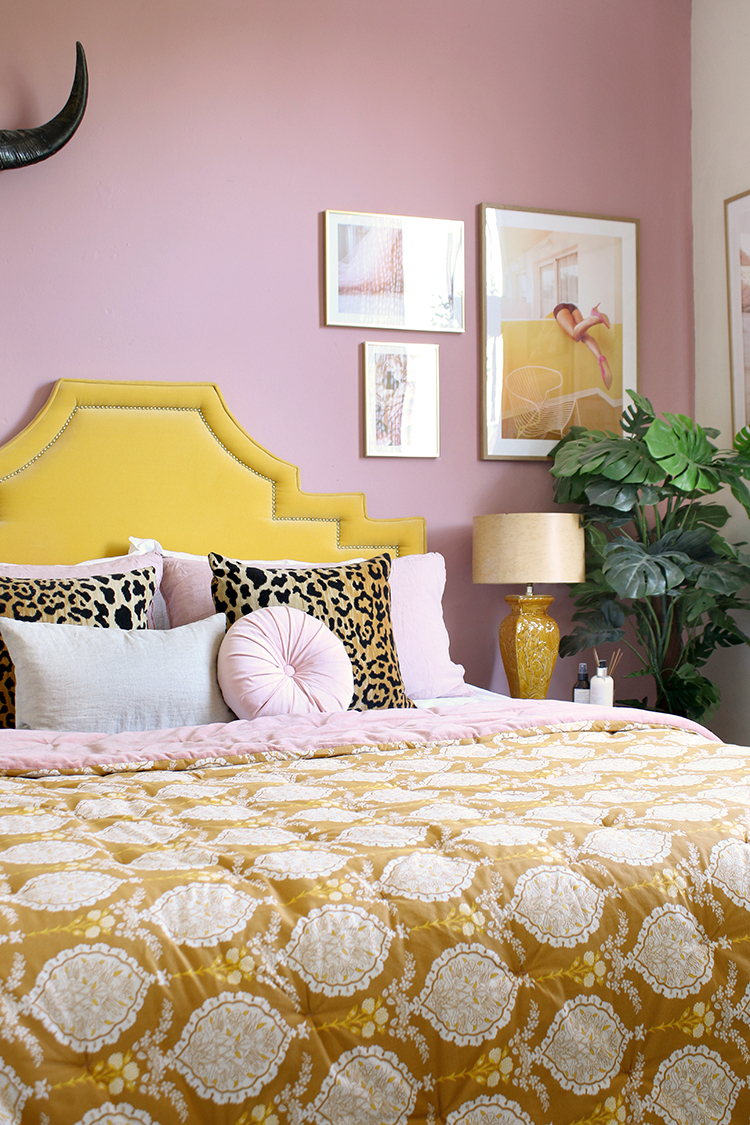 boho bedroom with patterned yellow bedspread against pink walls