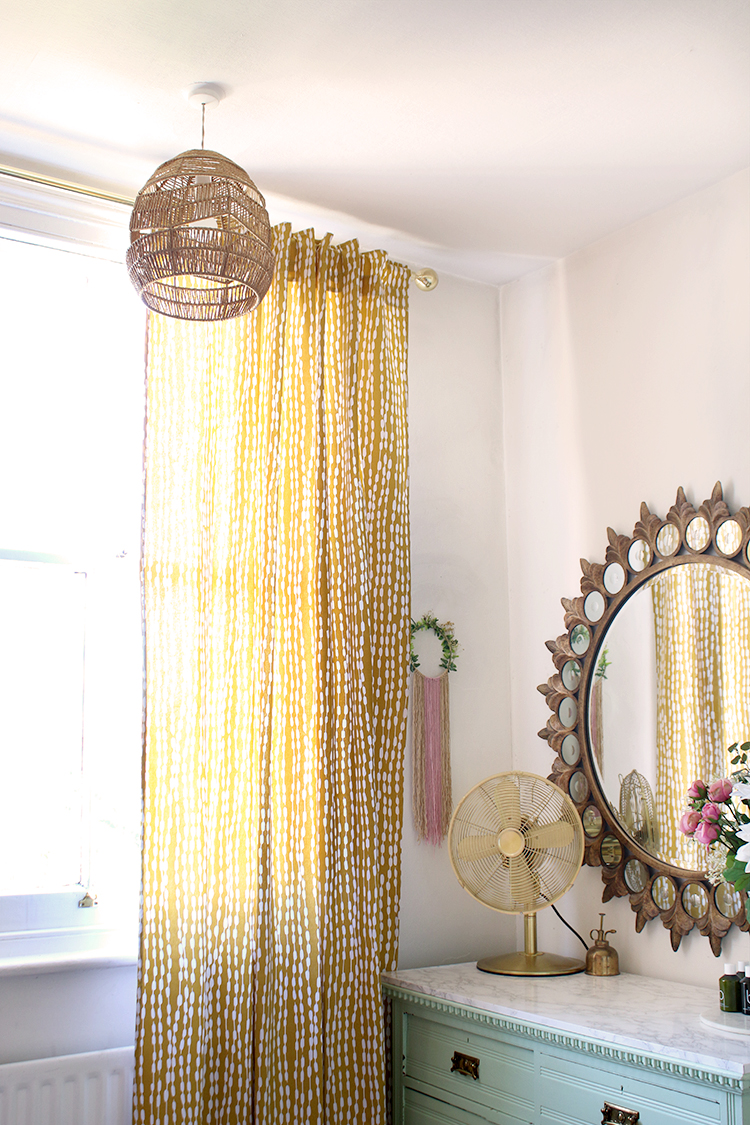 corner of room with yellow printed curtains and rattan light shade
