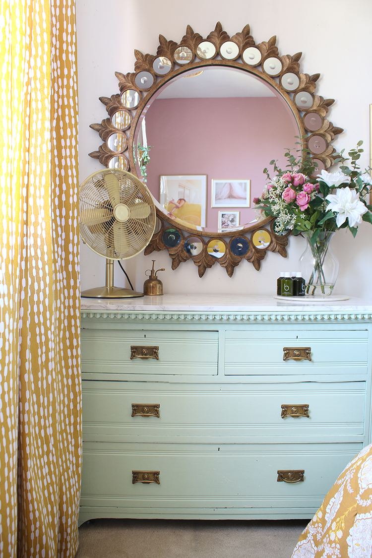 mint green chest of drawers with starburst mirror above