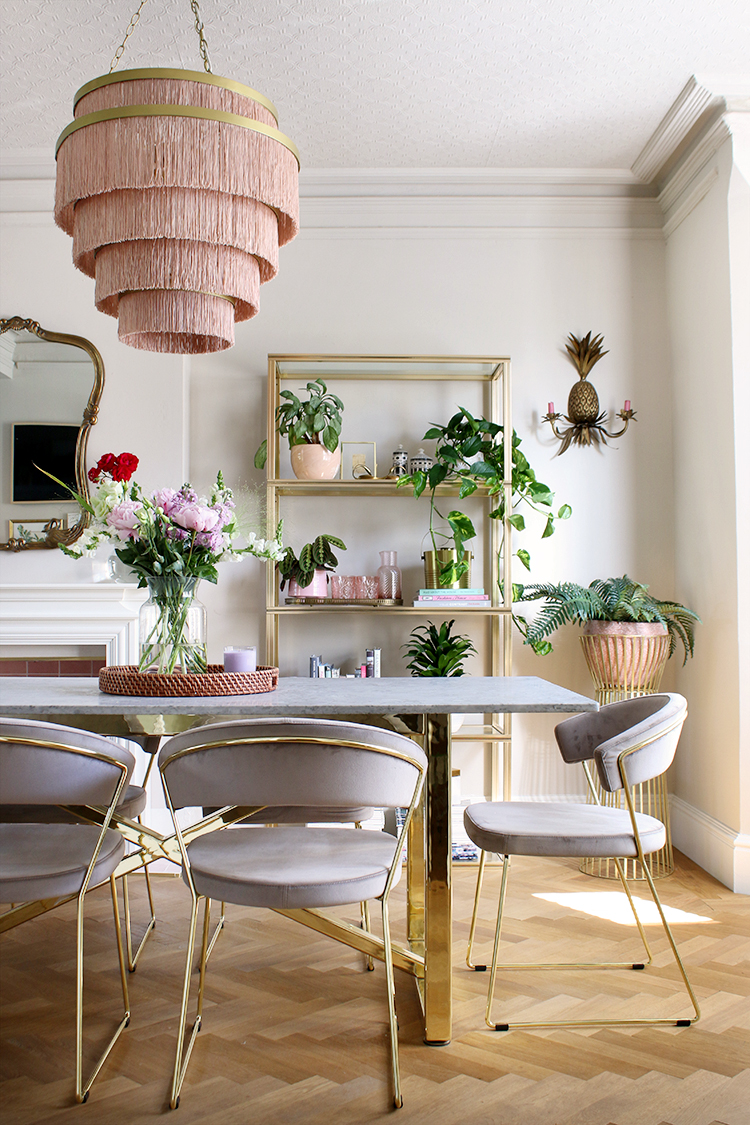 dining room in Victorian home with gold marble table and velvet chairs with large fringed ceiling light in pink