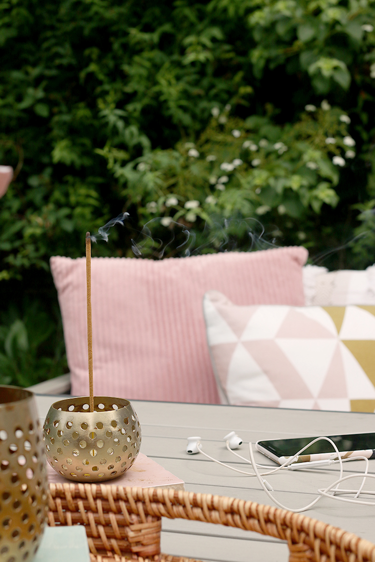 meditation in the garden - incense and mobile with headphones with pink cushions in background