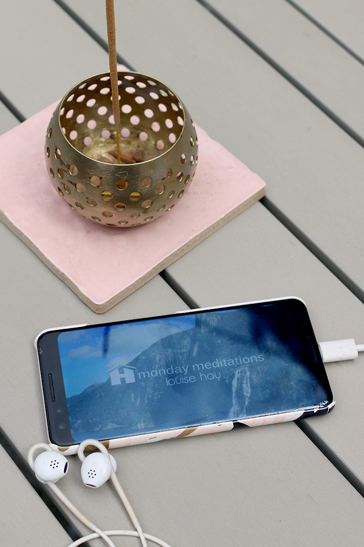guided meditations - mobile phone with earbuds with incense burning