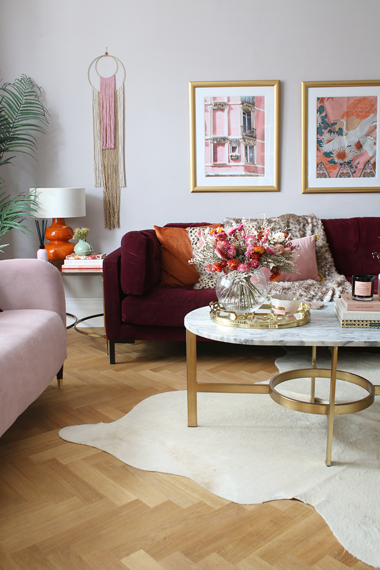 living room with burgundy and pink sofas and white cowhide rug with gold and marble accents