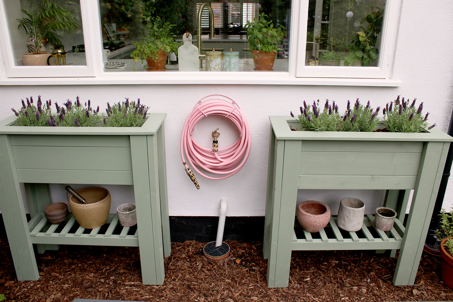 pair of sage green standing raised planters with pink garden hose under window