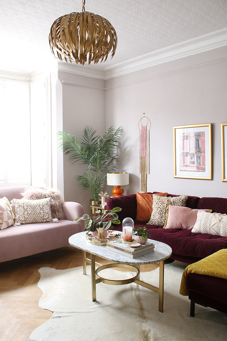 corner view of living room with pink and burgundy sofa in victorian home