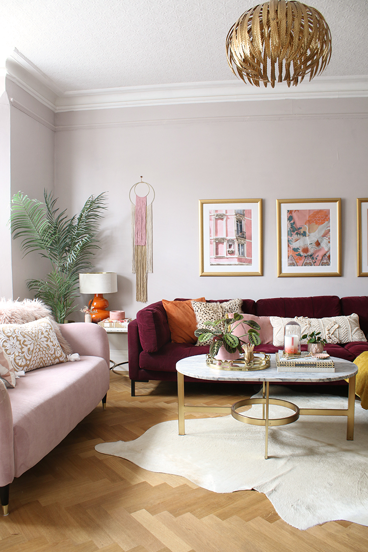 living room with burgundy and pink sofas with parquet floors and gold accents