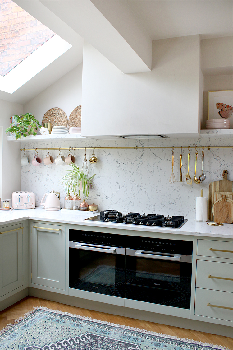 Pale Green Kitchen with marble effect worktops and pink accessories