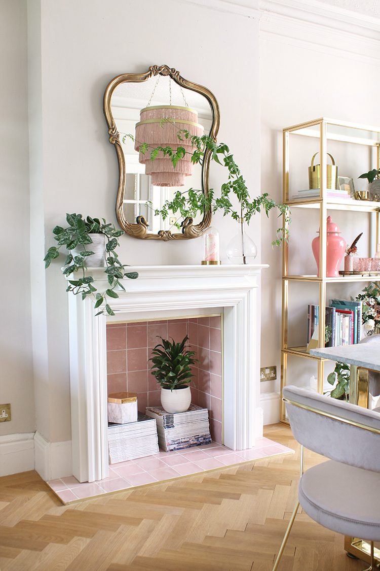 fireplace with pink tiles and plants