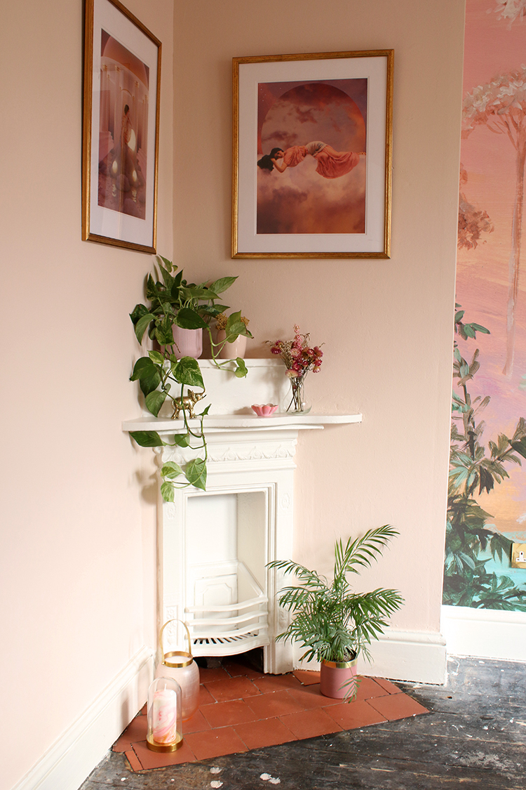 Victorian corner fireplace in peach room with plants and gold accents