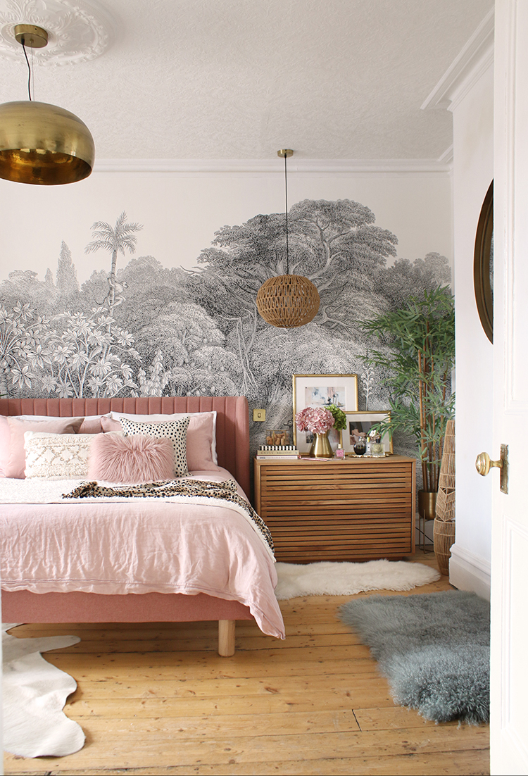 view into bedroom with wood floors pink bed wood chests and a wall mural