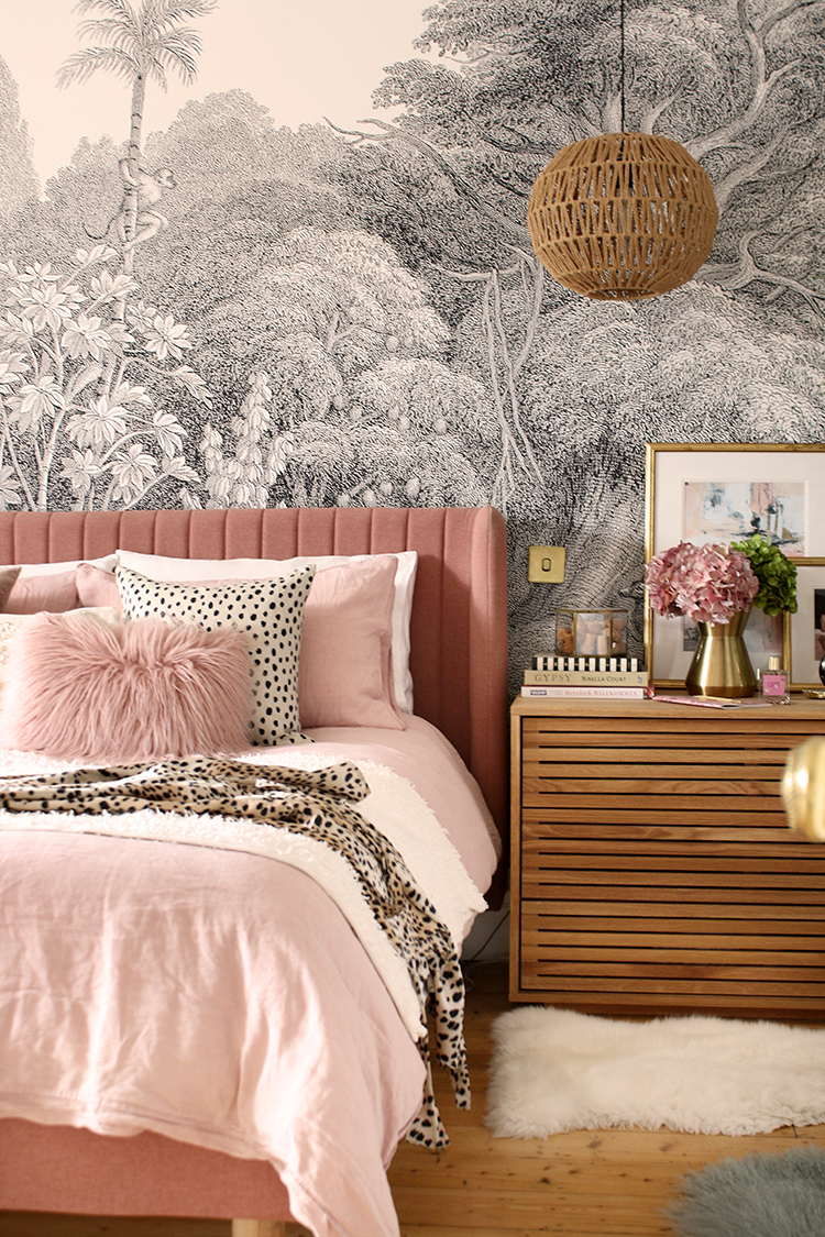 pink bed with black and white mural with a wood chest of drawers next to it