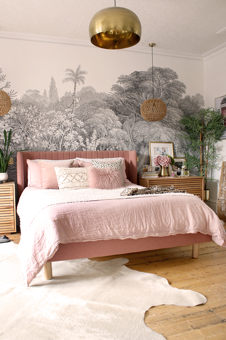 view of pink bed with cream linens on white cowhide rug