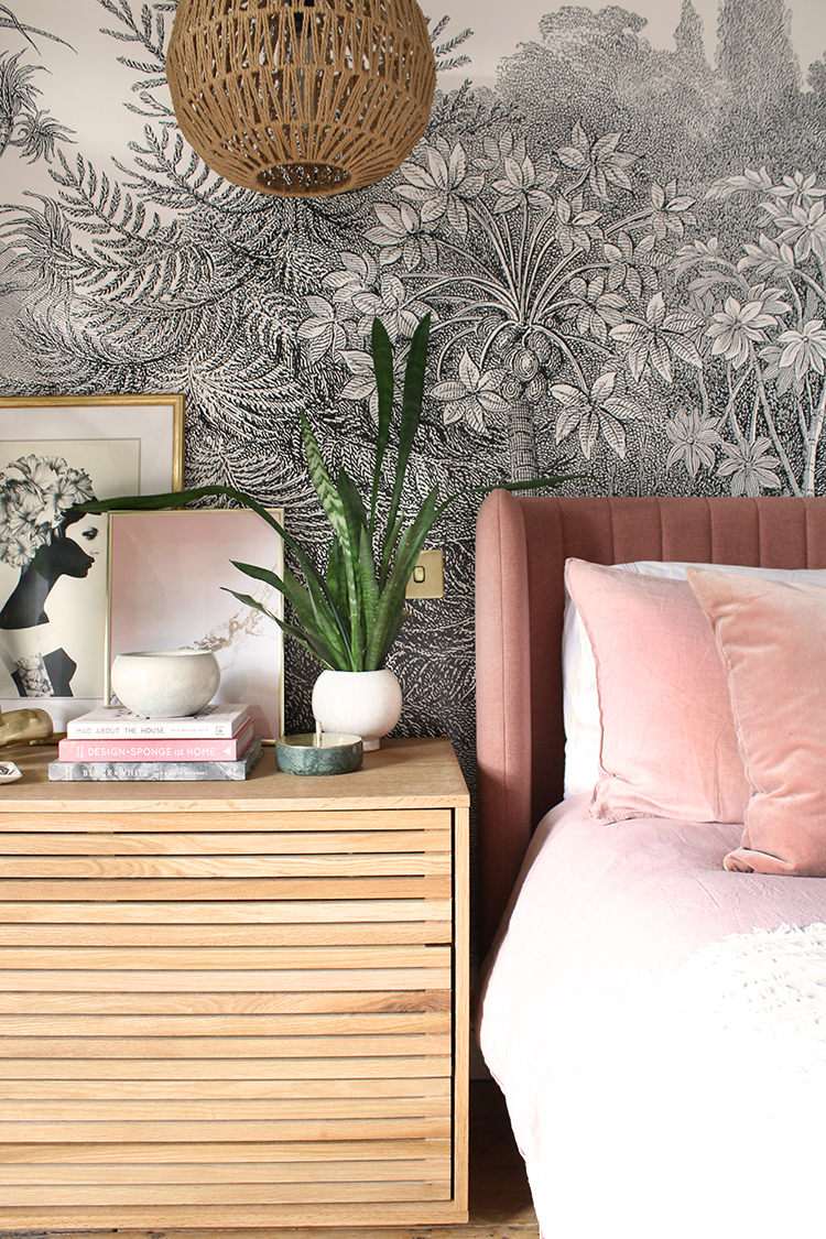 bedside table in wood with pink headboard plant and green plant
