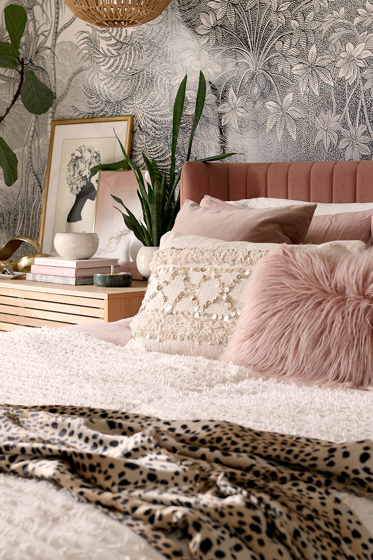 cream and pink bedding on bed with mongolian fur cushion and an animal print dressing gown on the foreground