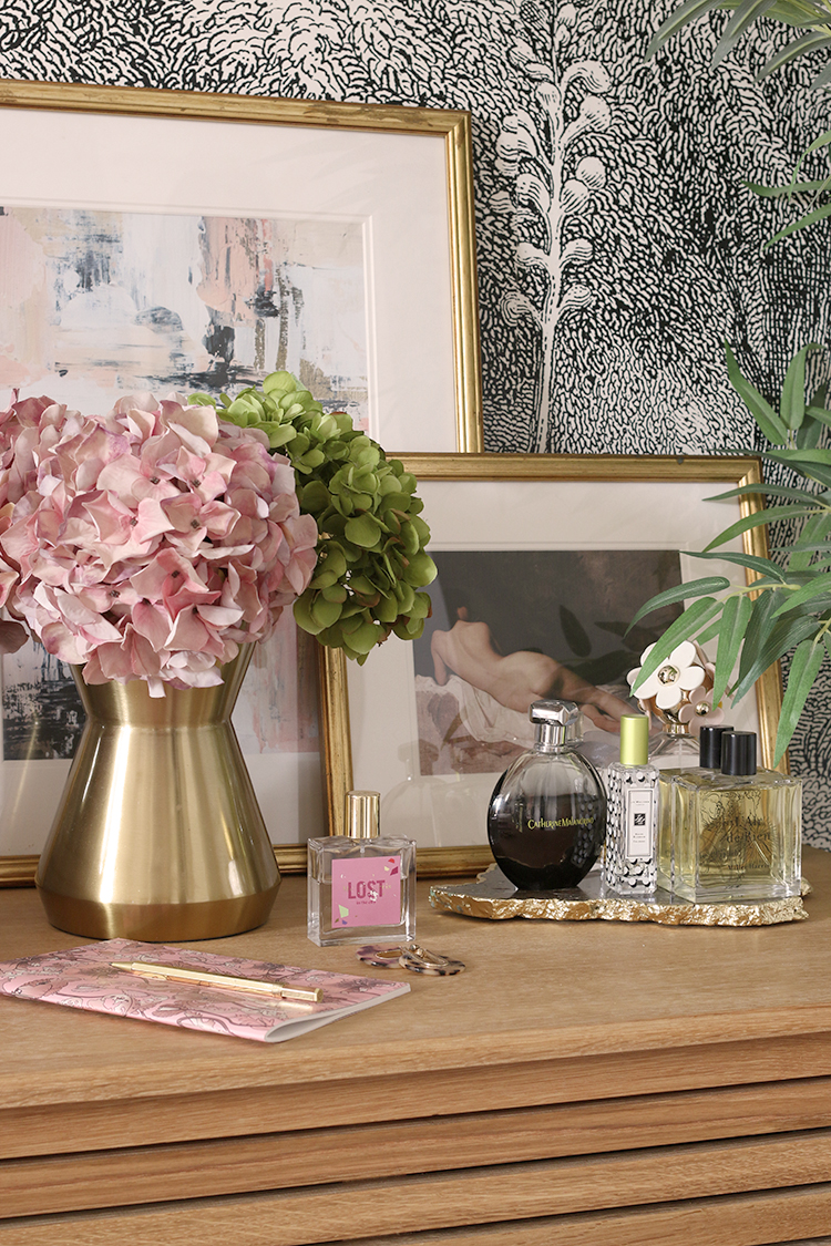 wood bedside table styled with pink flowers small artwork and perfumes