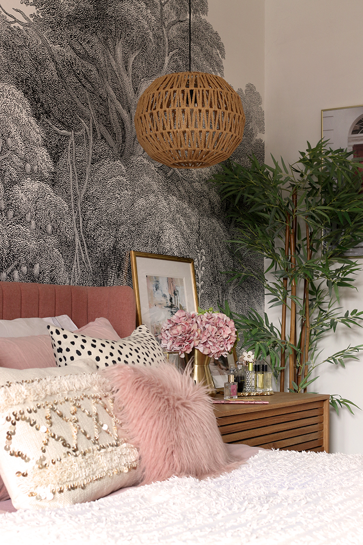 pink and cream cushions on bed with round woven pendant light in background