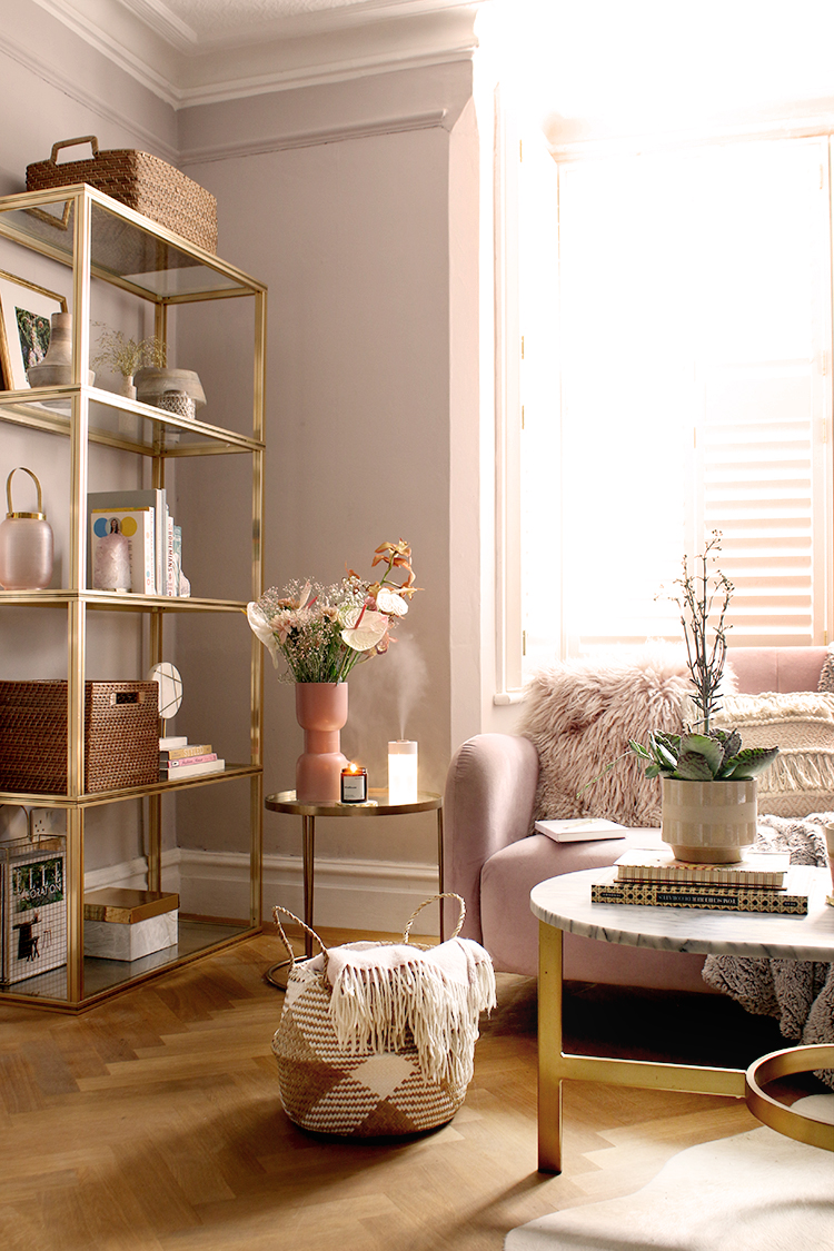 living room with pink sofa and brass shelving unit in calming colours