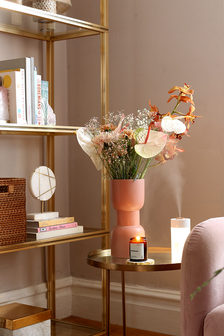 pink vase full of flowers on brass side table