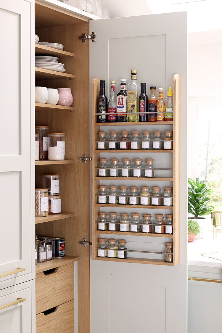 inside of a pantry with spice rack on door