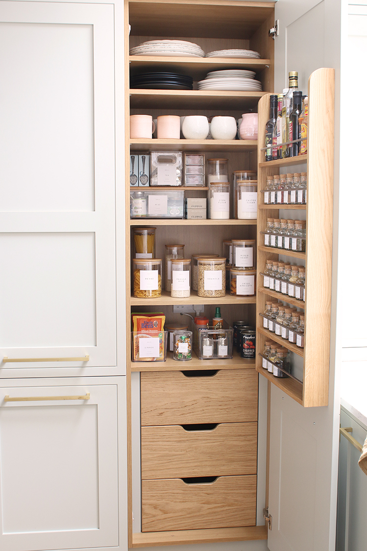 facing an organised pantry with the door open in a pale green kitchen