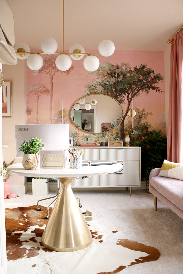 round marble and brushed brass desk in pink office with chest of drawers and mural in background