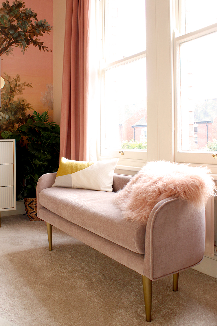 small pink sofa with cushions below large window