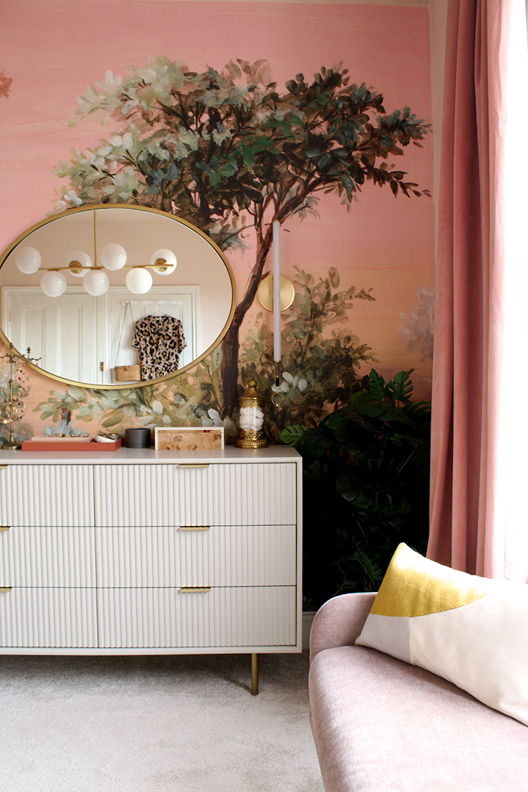 pale chest of drawers against pink and peach wall mural with small pink sofa in foreground