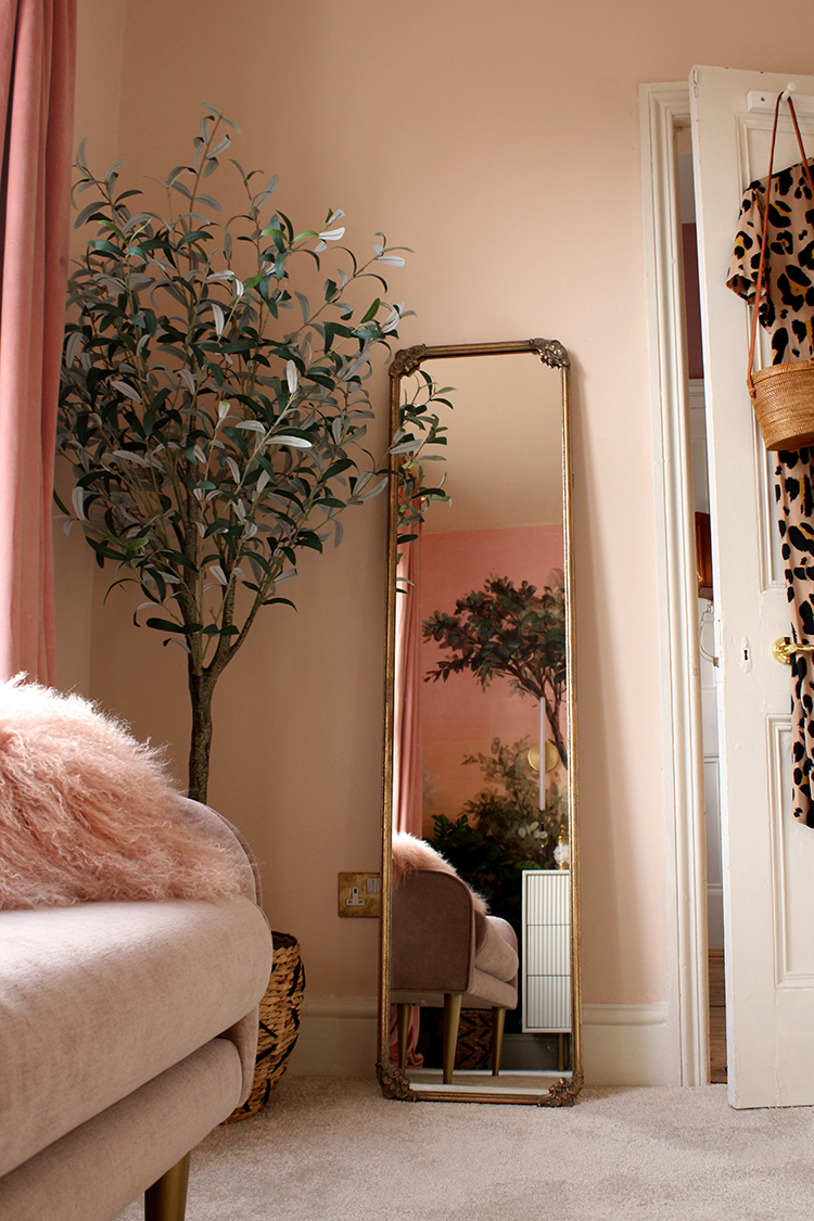 floor length vintage style mirror leaning against peach wall with pink sofa in foreground