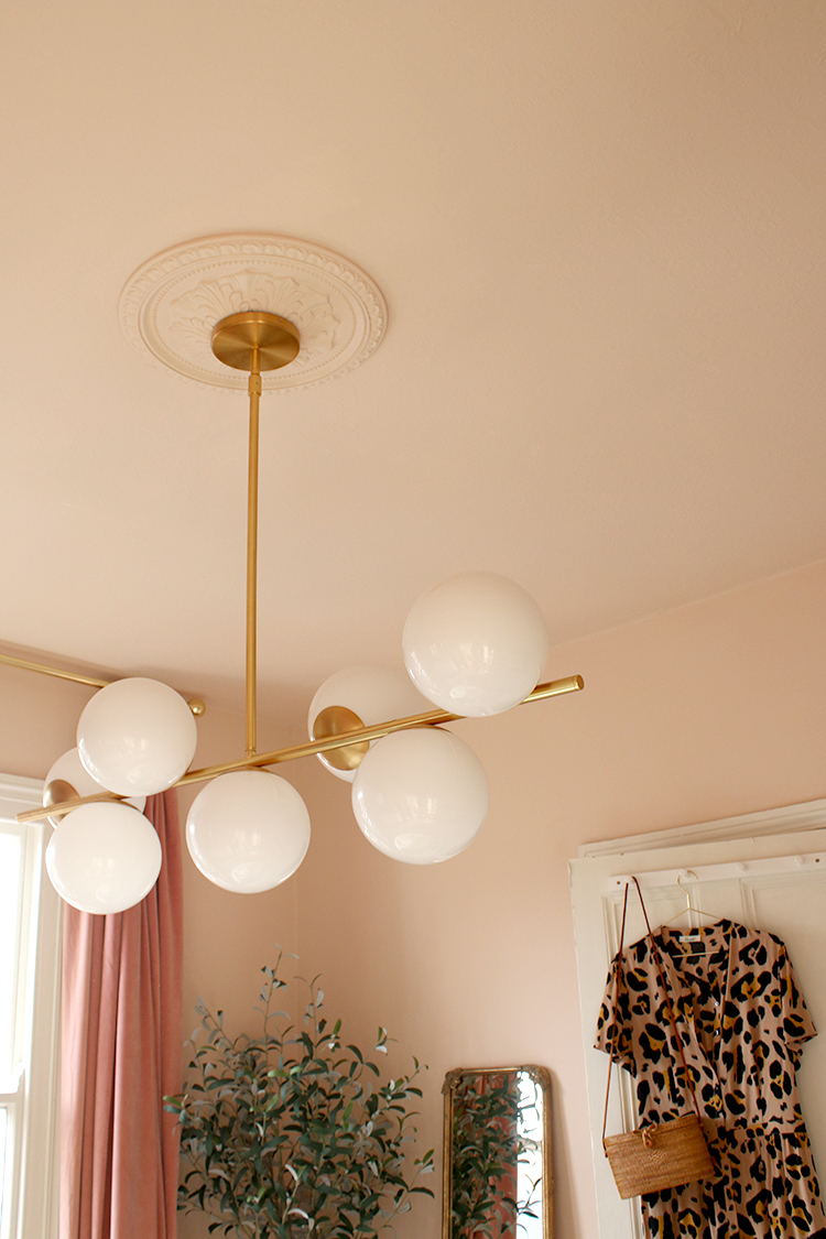 West Elm 7 Sphere light fixture with peach walls and ceiling rose