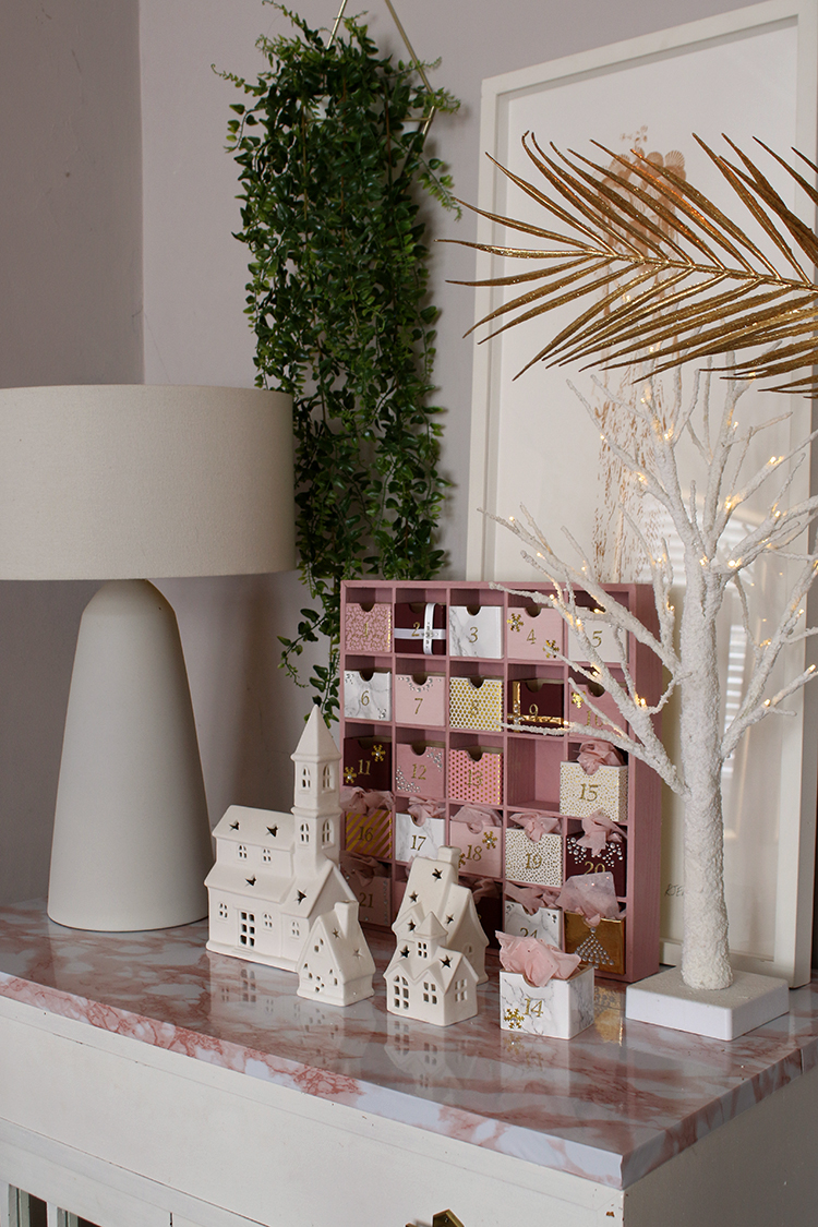 pink and white christmas decor styling on cabinet