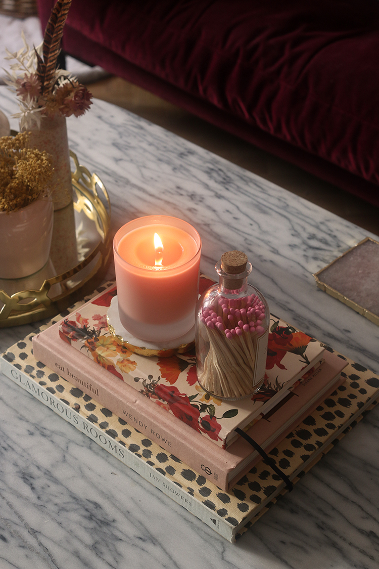 marble coffee table with peach candle and pink matchsticks in bottle