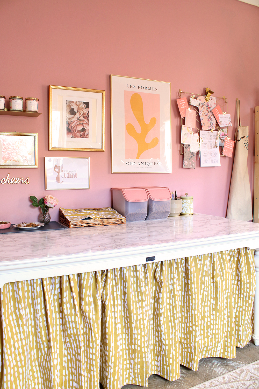 pet station in pink and mustard yellow utility room with gallery wall