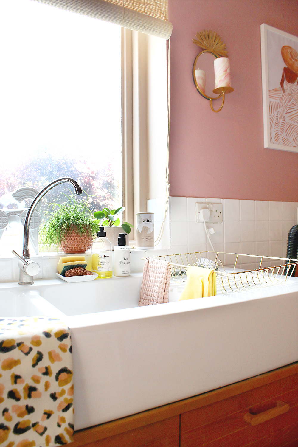 farmhouse style sink with leopard print teatowel and gold dish drainer